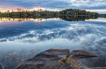 View over lake in sunset with the clouds in the sky reflecting in the water
