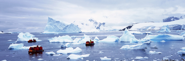 Panoramic view of ecological tourists in inflatable Zodiac boat with glaciers and icebergs in Paradise Harbor, Antarctica Wall mural