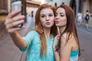 Two pretty girls taking selfie. Urban background. We love selfie.