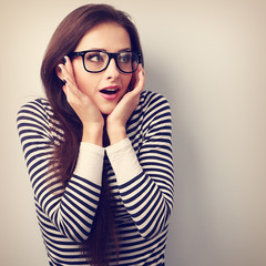 Fun surprising young woman in eyeglasses looking on empty copy s