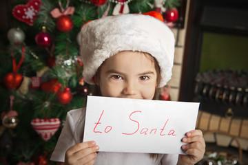 Little girl in christmas hat holding letter for Santa