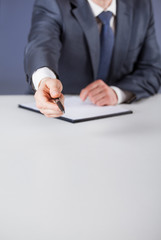 Businessman offering to sign a document