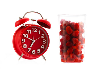 Red vintage alarm clock and raspberry, healthy breakfast concept