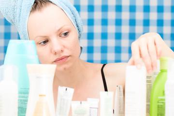Girl is choosing cosmetics in bathroom
