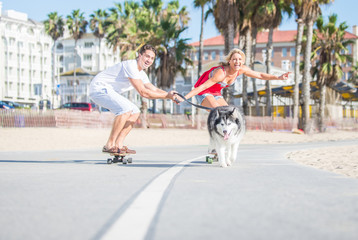 Happy couple and their husky dog making sport