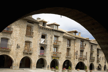 Arch view of Plaza Mayor, in Ainsa, Huesca, Spain in Pyrenees Mountains, an old walled town with hilltop views of Cinca and Ara Rivers