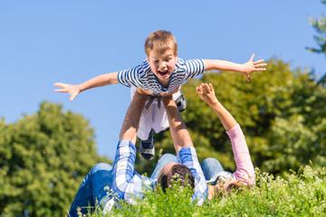 Familie spielt mit Kind im Gras auf der Wiese