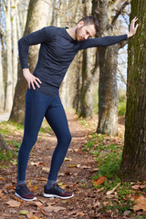 Runner doing stretching outside in autumn