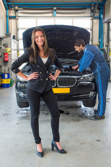 Sales woman standing in front of a car, being serviced for deliv