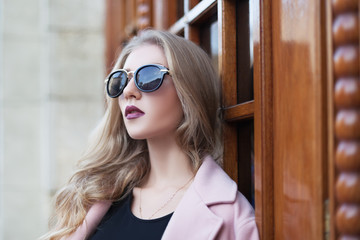 Beautiful young  fashionable woman with sunglasses looking aside. Female fashion. Closeup portrait