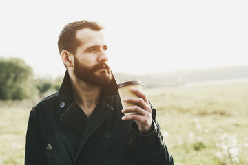 handsome bearded man with paper cup of morning coffee