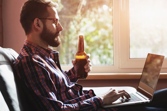 bearded man with laptop drinking bottle of beer