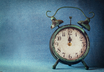 vintage clock over blue ice bokeh background. new year concept. selective focus