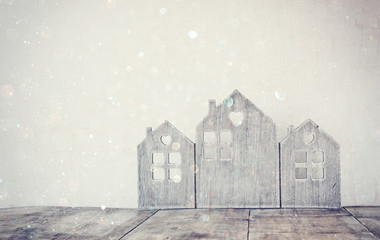 low key and abstract filtered image of vintage wooden house decor on wooden table. with glitter overlay. selective focus