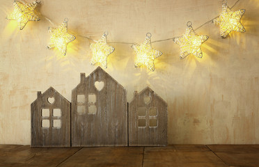 low key image of vintage wooden house decor on wooden table and stars garland. retro filtered. selective focus