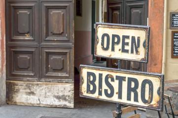 Vintage metal rusty Open Bistro sign on the street, in front of an open door
