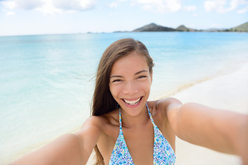 Summer vacation beach travel. Technology and people concept with smiling woman making selfie with smartphone on beach. Happy mixed race Caucasian / Asian Chinese woman taking self portrait having fun.