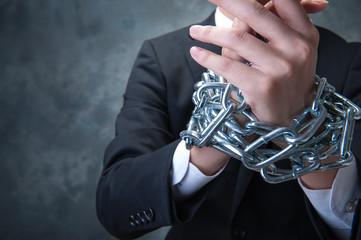 鎖を手に巻かれたビジネスマン