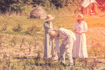 Group of people working in a field dressed in medieval white linen in Campus Galii in Messkirch