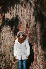 Woman Standing Besides a Big Tree Trunk
