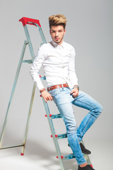 man leaning against a ladder while posing in studio