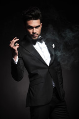 Handsome young business man enjoying a cigarette