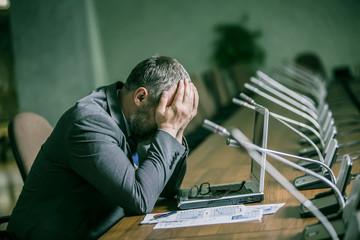frustrated businessman sits in despair his head in his hands at the conference table