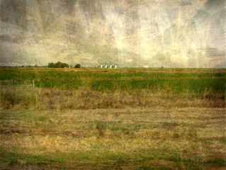 aged and worn vintage photo of farm in the distance