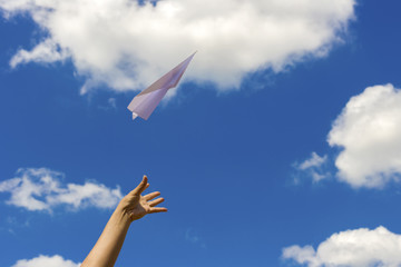 Throwing a paper airplane into the sky.