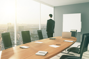 Businessman in modern conference room with blank board and city