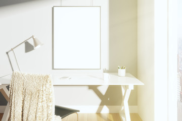 Blank picture frame on the wall in sunny room with lamp on the t