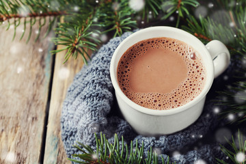 Wall Murals Chocolate Cup of hot cocoa or hot chocolate on knitted background with fir tree and snow effect, traditional beverage for winter time