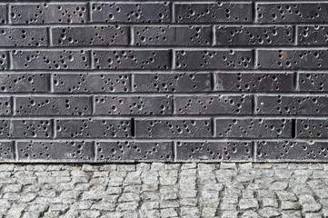 Modern dark brick wall with grey pavement ground