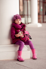 Portrait of cute baby girl holding toy dog in bag outdoors. Playful. Wearing trendy winter jacket, rubber boots, knitted hat. Looking away. Childhood.