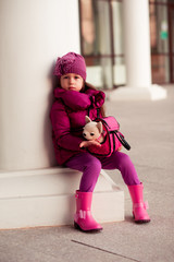 Portrait of cute stylish kif girl holding dog toy in bag outdoors. Looking at camera. Wearing trendy winter jacket, rubber boots and knitted hat. Childhood.
