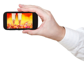 businessman holds smartphone with Xmas still life
