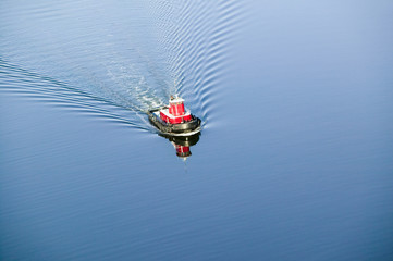 A aerial view of a bright red tug boat in blue water outside of Portland Maine