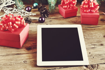 White tablet computer with Christmas gifts on wooden table close