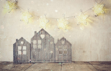 low key and abstract filtered image of vintage wooden house decor on wooden table and stars garland. selective focus