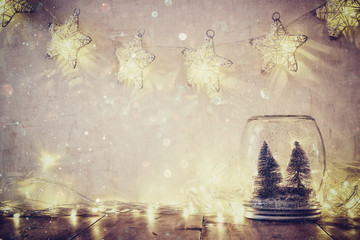 low key and vintage filtered image of christmas trees in mason jar with garland warm lights and glitter overlay. selective focus