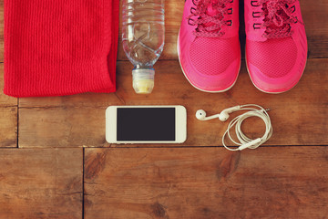 fitness concept with mobile phone with earphones, towel and woman sport footwear over wooden background.