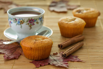 Still life with muffins, cinnamon and autumn leaves