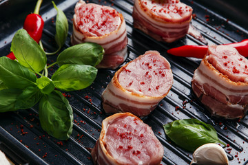 raw meat tenderloin medallions with bacon on the grill