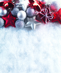 Winter and Christmas background. Beautiful sparkling silver and red Christmas decoration on a white snow background.