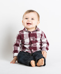 a cute 1 year old baby sits in white studio with jeans and a red white flannel looking and laughing looking above camera