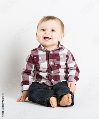 A Cute 1 Year Old Baby Sits In White Studio With Jeans And Red