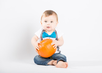 a cute 1 year old sits in a white studio setting with a pumpkin. The boy holds the pumpkin in his lap and looks happy. He is dressed in Tshirt, jeans, suspenders and blue bow tie