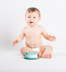 a cute 1 year old sits in a white studio setting. The boy is very excited to start eating his birthday cake. He is only dressed in a white diaper