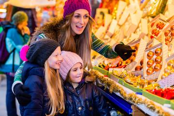 Familie kauft auf Weihnachtsmarkt Dekoration