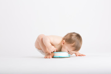 a cute 1 year old sits in a white studio setting. The boy takes a huge bite of cake on the floor with his face.. He is only dressed in a white diaper